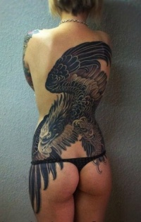Black flying eagle tattoo on whole back for women