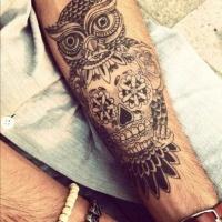 Black owl skull tattoo on arm