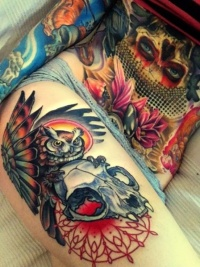 Coloured owl and skull tattoo on thigh