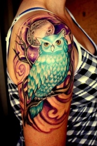 Coloured owl sitting on branch under moon tattoo on shoulder